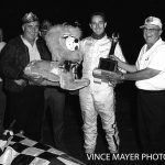 Illinois racer Roger West won his first USAC midget feature race at Chicagoland's Santa Fe Park Speedwy on July 19, 1968.  After his victory, West is joined in victory circle by USAC midget supervisor Bob Stroud (right) and a member of the local Lion's Club who is presenting West a stuffed toy lion for his winning effort.  (Vince Mayer Photo)