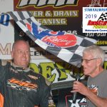 Jamie Lomax waves the checkered flag as announcer Dave Alger steps in to do a winner's interview.