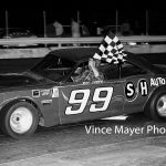 Ray Young carries the checkered flag at Waukegan Speedway in 1970.  (Vince Mayer Photo)