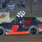 Brandon Shelhart carries the checkered flag after his win.