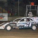 Nick Allen (#21) carries the checkered flag after his victory.
