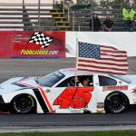 Fastest qualifier Rich Bickle Jr. (#45) carries the American Flag during the evening's opening ceremonies.