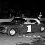 Ted Janecyk carries the checkered flag after scoring a win at Raceway Park in 1963.  (Bud Norman Photo)