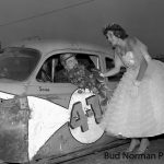 Behind the wheel of Stash Kullman's No. 4U, Ted Janecyk is either on the giving end or receiving end of a bouquet of flowers from his sister, Gail, who was Miss Calumet Park in 1957.  (Bud Norman Photo)
