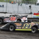 #B12 Kevin Weaver turned back the challenge from #14 Glen Thompson to win one of the three Late Model heat races last Saturday night. A steady rain shower fell on the speedway at the conclusion of the Sportsman heat race and officials were forced to cancel the remainder of the weekly program. Action will return this Saturday with a MARS Late Model series and Modified classes.