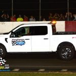 Albert Phillips behind the wheel of the Rod Baker Ford pace truck with photographer Chris Goodaker in the truck bed grabbing a few images.